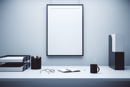 Blank picture frame on a wall and table with glasses, diary and coffee mug, mock up Stock Photo
