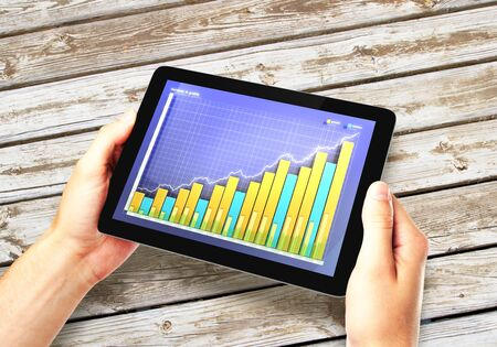 mobile marketing: Business chart on the screen of tablet with hands on the wooden table