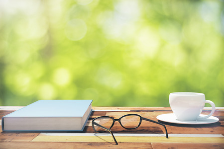 Book, cup of coffee and eyeglasses on a vintage wooden table in nature