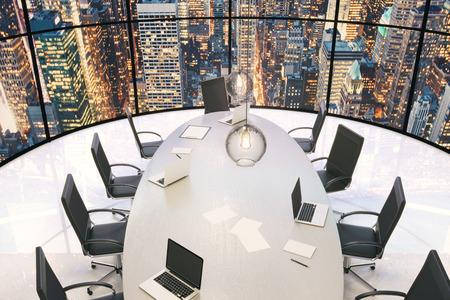 Conferentiezaal met houten tafel en een prachtig uitzicht op de stad 's avonds Stockfoto