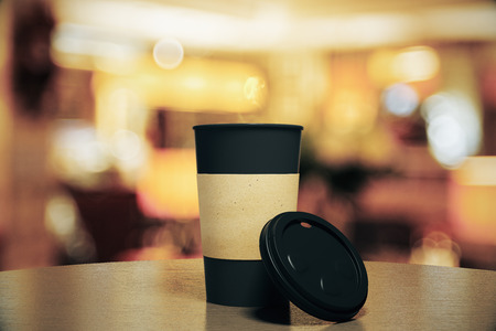 Blank black cup of coffee on a table at restaurant, mock up
