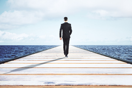 bridge in nature: Businessman walking on a straight road to the horizon Stock Photo