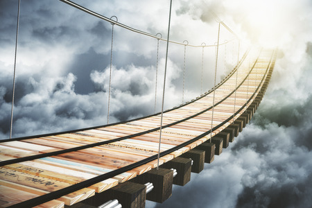 Wooden bridge in the clouds going to sunlight, concept
