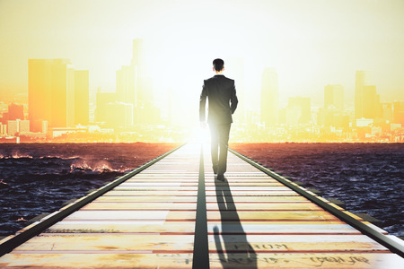 Businessman walking on a straight road to the big city at sunrise