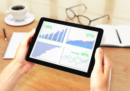 computer screen: Mens hands holding a digital tablet with financial charts Stock Photo