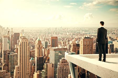 liderazgo empresarial: Empresario de pie en el tejado de un rascacielos y con vistas a la ciudad al atardecer Foto de archivo