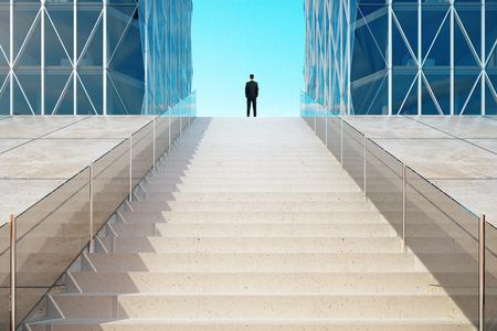 hombre de negocios: Empresario de pie en la parte superior de las escaleras cerca del moderno centro de negocios