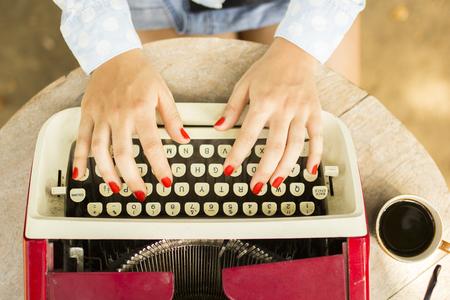 the typewriter: Muchacha que pulsa en la vieja m�quina de escribir con una taza de caf� al aire libre Foto de archivo