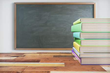 school desk: Pack of books on the wooden school desk with blackboard on white wall Stock Photo