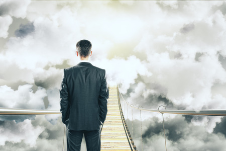 chasm: Businessman is walking on air bridge among the clouds concept