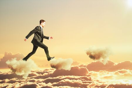 sunset clouds: Businessman is walking on clouds in the sky concept Stock Photo