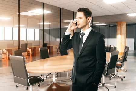 patron: Hombre de negocios hablando por teléfono en la sala de conferencias moderna Foto de archivo