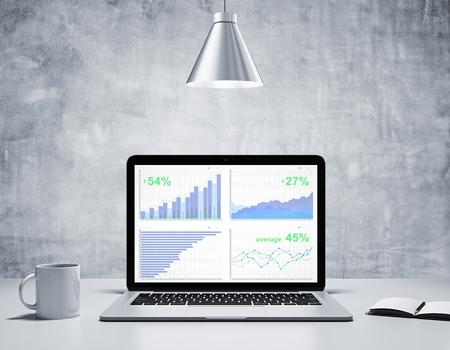 コーヒーのマグカップとラップトップ、銀色のランプとコンクリートの部屋で日記の画面でビジネス グラフ