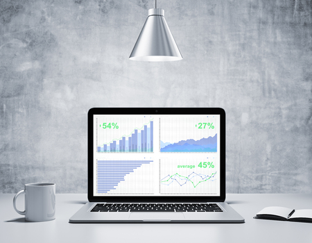 forex: Business graphs on screen of laptop with coffee mug, diary in concrete room with silver lamp