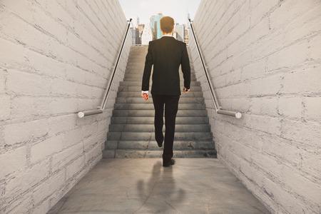 down the stairs: El hombre de negocios isclimbing por las escaleras entre paredes de ladrillo y piso de concreto