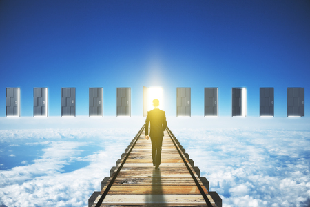 parallel world: Man walking to an open door in clouds concept