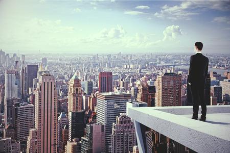 Ein Mann, der auf der Oberseite des skyscrapeer Blick auf die Stadt Standard-Bild - 47358942