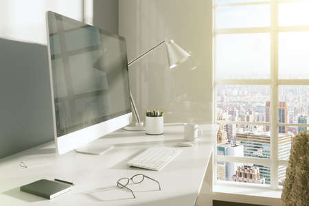 mock: Computer monitor with keyboard, glasses and lamp on white table in sunny room