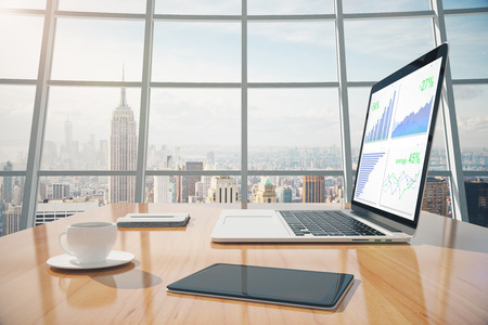 Business graphs on laptop screen, coffee mug, digital tablet on the table in sunny office with windows in floor Stock Photo