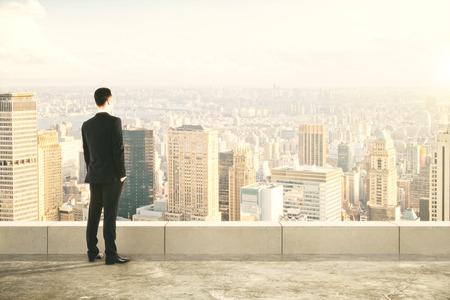 Geschäftsmann auf dem Gipfel des builng und Blick auf die Stadt Standard-Bild - 47358618