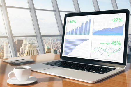 一杯のコーヒーとシティー ビューの日当たりの良い所で日記とノート パソコンの画面の上にビジネス グラフ 写真素材