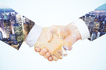 saludo de manos: Doble exposición con un apretón de manos entre dos hombres de negocios