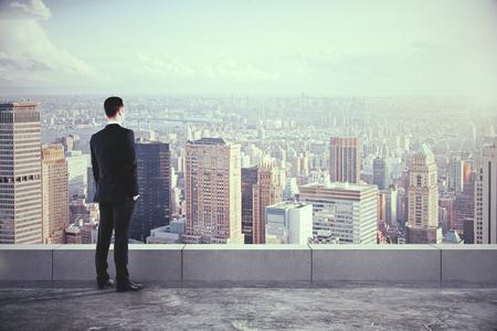 jefe: Hombre de negocios en el techo y mirando a la ciudad con rascacielos