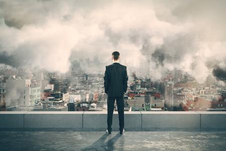 ciel avec nuages: Homme d'affaires sur le dessus du b�timent et en regardant la ville brumeuse