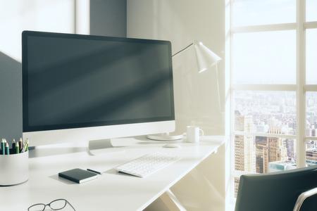 monitor de computador em branco com vidros, diário e outros acessórios na tabela branca no quarto moderno Editorial