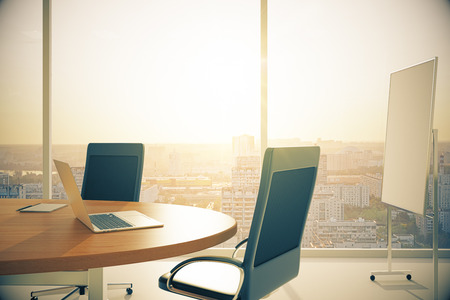 Conference room with wooden table with laptop and blackboard at sunset