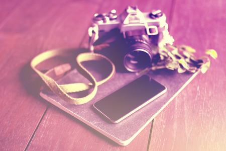 publicist: Blank smartphone screen, old style camera and diary on wooden floor, instagram photo effect Stock Photo