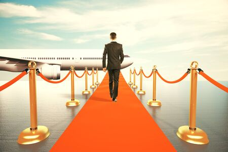 first plane: Businessman walking on red carpet to the first class of plane