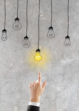 graphic backgrounds: Hand goes to glowing light bulb, idea concept