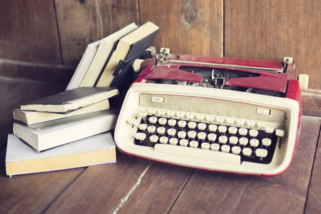 old desk: Old style typewriter with books on wooden floor