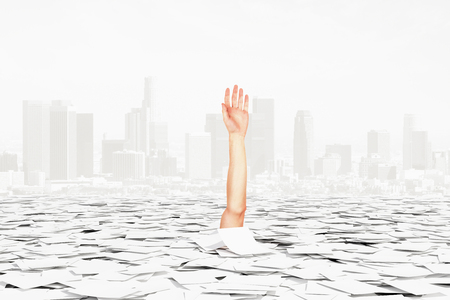 Human hand sticks of pile of paper on the city background, bureaucracy concept Stock Photo