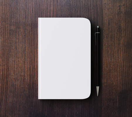 diary: Blank white diary cover and pen on brown wooden table, mock up Stock Photo