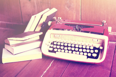 publicist: Old style typewriter and books on a wooden floor