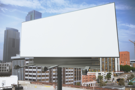 billboard: Blank white billboard on a background of buildings, mock up