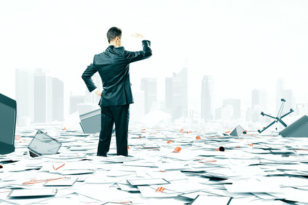 paperless: Businessman looking at the horizon among office stuff chaos Stock Photo