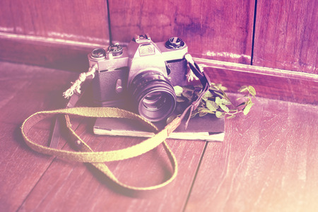 publicist: Old style camera with diary on a wooden floor