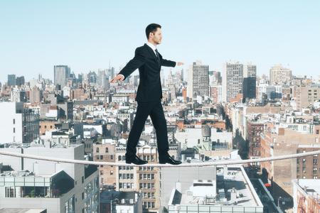gestion empresarial: El hombre de negocios est� caminando sobre una cuerda en el fondo de la ciudad