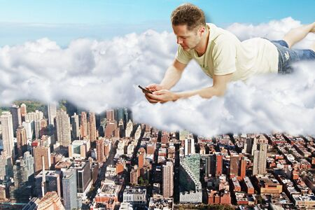 megapolis: Man lies on clouds with smartphone above megapolis city concept Stock Photo