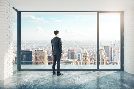 Zakenman in lege zolderkamer met groot raam in de vloer en uitzicht op de stad Stockfoto