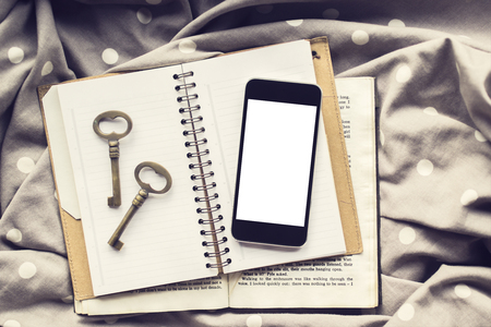 hp: Blank smartphone screen with vintage keys on blank diary and book, mock up