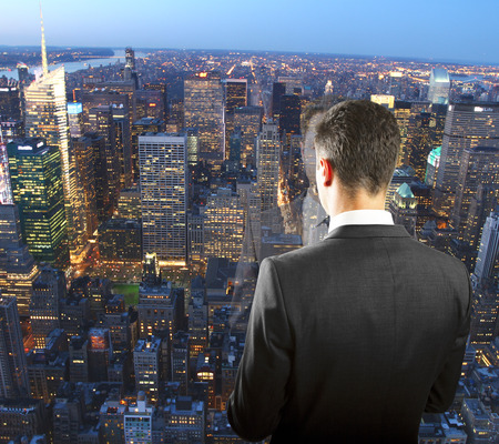 out of business: Businessman on the top of skyscraper looking at night megapolis city
