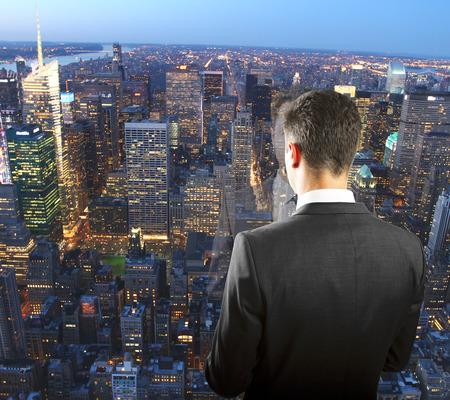 haciendo ejercicio: Hombre de negocios en la parte superior del rascacielos mirando la noche megapolis ciudad Foto de archivo