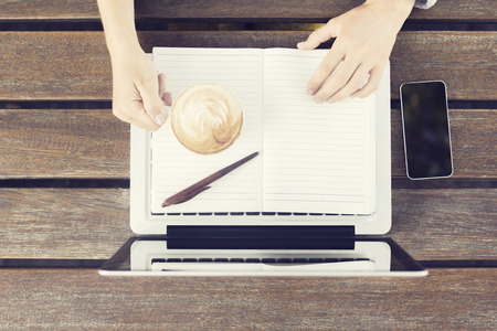 univercity: Girl with laptop, coffee mug, blank diary and cell phone on wooden table