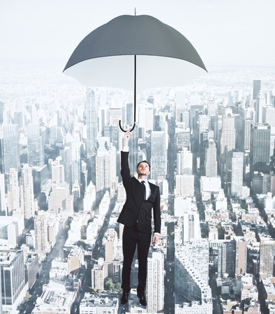 megapolis: Flying businessman with umbrella at megapolis city background