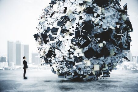 reaches: Businessman and big heap of office stuff at city background