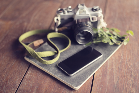 publicist: Vintage camera, blank smartphone, diary and leaves on wooden table Stock Photo